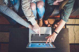 Jovens sentadas diante de um canal de marketing de comunidade