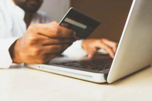 Homem sentado na frente do computador segunrando cartão de crédito prestes a realizar uma compra de eCommerce