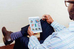 Homem sentado fazendo análise do seu eCommerce pelo tablet