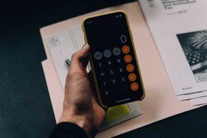 mão segurando celular aberto na calculadora prestes a calcular a quota do simples nacional