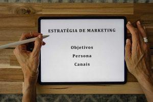 tablet sobre mesa em que se le estrategia de marketing objetivos personas e canais