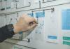 detalhe de uma mão organizando um plano de negócio em um quadro com vários adesivos e alfinetes