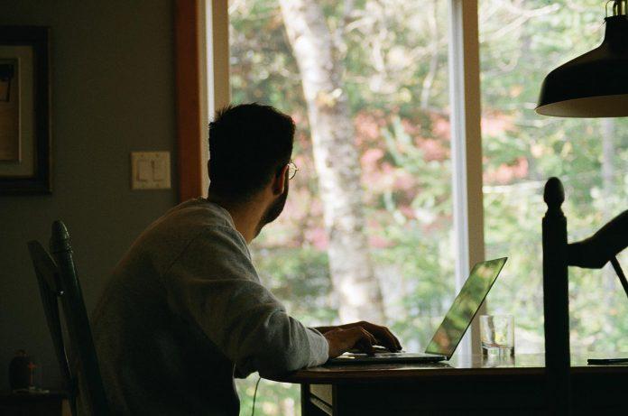 homem sentado no escritório de casa diante de computador olhando pela janela