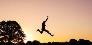 empreendedor saltando sobre lago ao por do sol